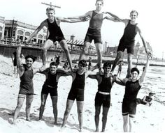 Young men on a beach forming a lop-sided human pyramid - USA, 1930s