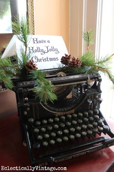Have a Holly Jolly Christmas - vintage Underwood typewriter with garland from HomeGoods that is cut apart and tucked here and there throughout the house - great idea! eclecticallyvintage.com HomeGoodsHappy HappybyDesign sponsored