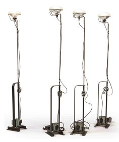 A SET OF FOUR CHROME STEEL AND METAL 'TOIO' FLOOR LAMPS Designed by Achille and Pier Castiglioni in 1962, produced by Flos, Italy, Second half 20th Century Each with adjustable stand and the top mounted with a front-light from a car, on black metal base and integrated Flos Cubo transformer 173 cm. high (4)