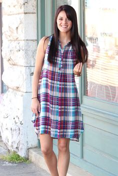 "We love plaid and all the bright colors in this dress! Buttons 1/4 of the way down the front and features pockets on the side! Very lightweight and cool for the summer. Non-sheer. Blue in color with fuchsia, ivory, light blue, and gold mixed in.  Model is 5'9"" pant size 2 wearing size small. Fits true to size.S(0-4) M(6-8) L(10-12) 100% Rayon."