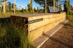 donor recognition etched in a blackened steel band inset in a bench made of recycled wood.