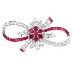 Palladium, Ruby and Diamond Bow Brooch, Tiffany & Co. - Centering a cluster of 7 round rubies, the looped bow accented by 22 square-cut rubies, altogether approximately 2.45 cts., set with 38 round diamonds approximately 2.00 cts., signed Tiffany & Co., circa 1940, approximately 5.8 dwts.
