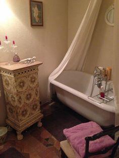 Jolie salle de bain avec une belle baignoire aux pieds de lion.