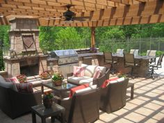 Outdoor living area - including a fireplace, built-in grill, outdoor stainless refrigerator, granite bar that seats 6, and an eating area. The furniture is from Restoration Hardware.