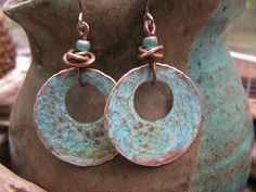Handmade Copper Ring Earrings - the copper rings are first hand created, hammered, textured, filed and touched with patina prior to sealing to maintain the rich but soft coloration. I have chosen to create a hand twisted copper wire beads to compliment the blue green highlights of the light patina on the rings. Sterling Silver earring wires are oxidized to highlight the old world feel. Approximate Size: 1 inch ring with 1 inch wires. For your convenience, your earrings will be mailed with…