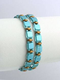 Náramok šitý zo zlatých voskovaných matných korálok a tyrkysových štvorčekov. Náramok sa 2x omotá okolo ruky. Zapínanie z bižutérneho kovu...
