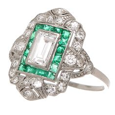 Diamond Platinum Engagement Ring. Circa early 1930s Platinum, Diamond and Emerald Engagement Ring, centrally set with a stepped cut, Emerald Cut Diamond that is 3/4 carat and is H in Color and VS in Clarity, surrounded by Emerald cut Emeralds of Fine Color. The ring is further set with Transitional cut Diamonds of the period totaling 1/2 Carat. 1930s