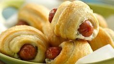 """Cheesy Crescent Underdogs-Give your team a leg up with """"underdogs"""" – a bite-sized Crescent dog with a surprise of chive and onion cream cheese and green olives under the dog! http://www.pillsbury.com/recipes/cheesy-crescent-underdogs/6edfe655-e28d-41f9-a68e-ad26460154f6"""