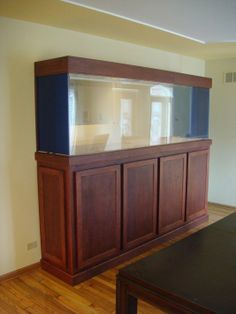 Aquarium Stand Price range $2,000 - $3,000 This cabinet was made to order for the client's aquarium. It features hinged doors to access storage below and a wood top to hide the tanks cover. The material is cherry.