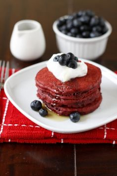 red velvet pancakes with whipped cream and blueberries.