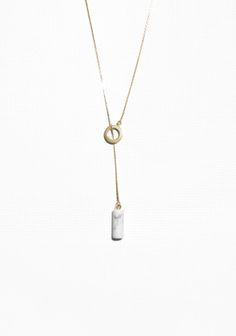A marble-like gemstone anchors this sophisticated lariat necklace crafted from brass with a shiny gold-tone finsh.