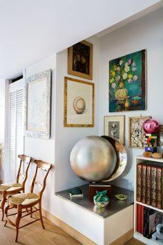 House tour: Rosita Missoni's quirky and colourful country home: In the hallway, a mix of antique chairs, paintings and an orbital silver sculpture sets an eclectic scene.