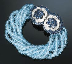 A Sapphire, Aquamarine and Diamond Bracelet by Cartier The clasp designed as a circular and oval-cut sapphire cluster within a pav-set diamond surround to the eight strand faceted aquamarine bead torsade, circa 1955, with French assay and maker's marks, 22.5 cm lon
