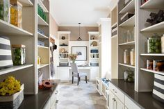 Chic, long kitchen pantry boasts ivory cabinets topped with charcoal gray quartz and modular shelving units filled with glass canisters and The Container Store Rugby Stripe Bins facing each other across from a white and gray hex tiled floor which leads to the work space.