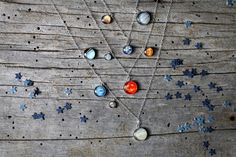 This is a truly stunning, delicate, layered necklace that celebrates our home in the cosmos - our solar system. All of our planets, even Pluto, are represented as well as our Sun. Each planet or star is set in a delicate bezel pendant that is place sporadically on one of the 3 layered chains. The chain lengths are 24, 20, and 16. The 2 finishes that are available are 14k gold fill or sterling silver. An elegant way to pay homage to our galaxial home. Also looks beautiful with these earrings…