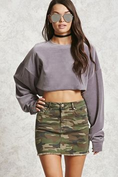 A mini denim skirt featuring allover camo print, a five-pocket construction, a zip fly, and a frayed hem.