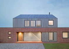A timber box with a pitched roof sits atop the handmade-brick ground floor of this house in the English village of Orford by Nash Baker Architects