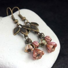 These handmade earrings are made with 6mm pink flower-shaped czech glass beads, 5mm pink melon-shaped czech glass beads, 5mm beige flower-shaped czech glass beads, and 12mm leaves-shaped brass connector beads. The french hooks with ball are made of brass and they are nickel