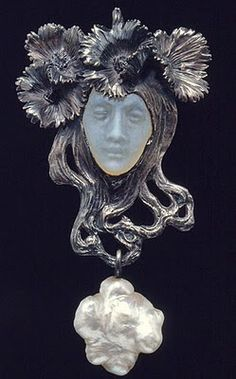 RENÉ LALIQUE. 1900 signed 'Female Head with Poppy Blossoms' Pendant in the form of a woman's head, with a baroque pearl at the base hanging from her hair. Thick tresses of hair and a crown of four dark blue enamel and chased poppy blossoms frame the face of molded green glass. Calouste Gulbenkian Museum, acquired from the artist in 1901.