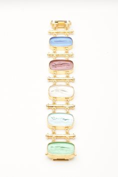 This bracelet is quintessential Elizabeth Locke.  It is made of 19kt hand-hammered yellow gold while 5 venetian glass engraved intaglios are displayed in a variety of pastel colorations. The rectangular shaped intaglios are set over mother of pearl to enhance the color.  The bracelet measures 7.75 inches in length