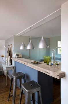 On a installé un beau plan de travail en bois dans cette cuisine de loft ouverte. Les tabourets en métal et les suspensions très basses créent l'illusion d'être au comptoir d'un bar typiquement parisien dans cette spacieuse cuisine américaine.