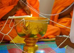 Ceremonial water bowl with candles and sacred thread during blessing by monks. Monk Blessed String Bracelets in Thailand (Sai Sin Sacred Thread). String blessed by monks to bring good luck and protection. Traditions and Culture in rural Thailand (Isaan) by http://potatoinrice.com/