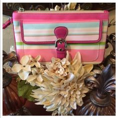 "Coach Hampton Wristlet  Authentic Coach Hampton Wristlet. The exterior has some faint marks. Please see pictures. Clean interior. Has leather strap trimmed in hot pink. Wristlet colors of pink, green, blue, and white. Beige interior. Coach hang tag is missing. Front pocket gives you extra storage. Measures approximately 7 1/2"" W X 4 1/2"" H. Thanks so much for stopping by!!!  Coach Bags Clutches & Wristlets"