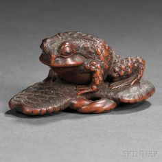 "Wood Netsuke of a Frog on a pair of sandals, Japan, 19th century, signed ""Yoshitada"" on a rectangular cartouche to base, ht. 3/4, wd. 1 3/4 in."