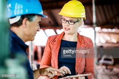 Stock Photo : Female Architect And Construction Worker Discussing On Site