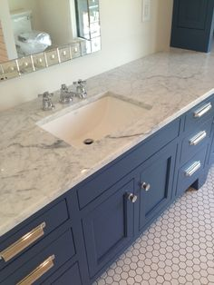 Marble counter, slate blue cabinets, hex tile and modern handles