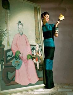 """""""Model wearing dinner-sheath of water-marked silk, with Chinese lines, standing with a fan next to Chinese painting."""" Photo by John Rawlings, 1941"""