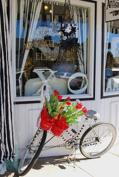 a bike with a flower basket out the front of my shop
