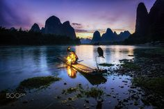 """Old cormorant fisherman on a small bamboo boat in xingping, china. It was amazing experience photographing the fisherman with the sunset over the karst mountains.   For Prints:  <a href=""""http://fineartamerica.com/featured/the-cormorant-fisherman-insung-choi.html"""">Fine Arts America</a> For more: aaron90311@gmail.com <a href=""""http://www.facebook.com/lifesolyrical""""> FB Page </a> <a href=&qu..."""