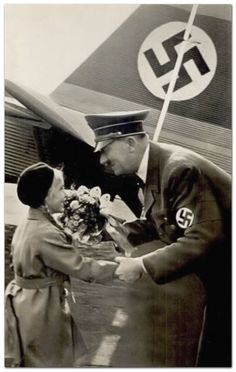 Adolf Hitler accepting flowers from an adoring child upon arrival by the Fokker tri-motor seen in the background.