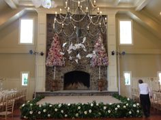 Stage with a wrap of flowers, topiary's lining the fireplace, and butterflies from the chandelier - Designs by Crest Florist