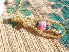 """Nothing beats Swarovski Austrian Crystal for a little bling and sparkle.  Artisan lampwork pink and blue rondelle bead is matched with Bermuda blue crystals, wire captured and caged.  Accented with coils and gold plated beadcaps and spacers, a unique pendant.  Gold plated dainty cable chain with spring ring clasp, a beautiful addition to any handmade jewelry collection.       Necklace is 17-1/2""""   Pendant measures 2-1/4 x 3/4"""" with a dainty, very feminine look.      Thank you for shopping…"""