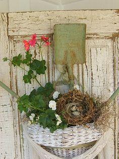 Wreath with geranium, nest, basket and the hook is a garden shovel.