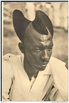 "From the Tutsi of Rwanda/Burundi. This hair design is called ""Amasunzu"".  Amasunzu had more than 30 forms and was common among teenagers, the youth and, in some cases, adult men. The style is designed by cutting some of the hair sideways, towards the middle, then leave it to grow.  It was used by the Ancients, and is still used today."