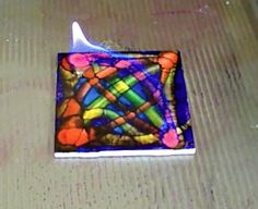 By beetlewing. Place ceramic tile in metal jelly roll pan. Apply darker color of alcohol ink all over tile. Immediately light with lighter. Fire burns out once alcohol is consumed. Apply thin line of lighter color over top and light immediately. Repeat for other lines and colors of alcohol ink.