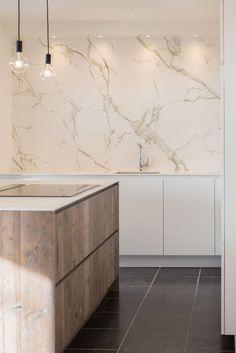 Eigentijdse keukens - Keukencenter Geusens  Strakke elegantie met een stoere knipoog  De opzetkasten met de toestellen onderscheiden deze kolomkastenwand van het stereotype.  Door creatief om te springen met de diepteverschillen, krijgt dit ontwerp een vernieuwende dimensie.  Zo kan er in deze beperkte ruimte een volwaardige keuken worden gerealiseerd.  Het strakke wit  krijgt extra karakter door de combinatie met de klassieke marmerlook en het robuuste hout.