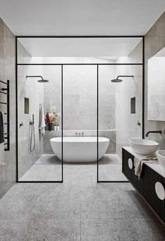 Bathroom: A generous master bathroom features a freestanding bathtub, twin showers, and ample space. A black vanity against plays host to twin basins. | Alisa and Lysandra gave an old Melbourne home a modern renovation
