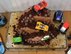 over head how of A monster truck cake covered in chocolate candies and figured from blaze and the monster machines on an old cookie sheet with a white background