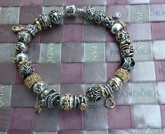 My first Pandora bracelet, love the combination of the two toned beads with the gold spacers and clips...the weave is thanks to Natalie Page who makes them from Pandora ribbons...pretty cool.