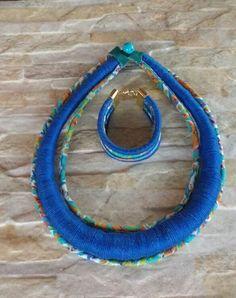 Colar com uma corda engrossada simetricamente e trabalhada com linha azul, duas cordas trabalhadas com tecido estampado Pulseira com quatro cordas cobertas com linha e tecido Acabamento dourado!