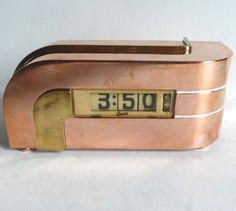 Kem Weber Zephyr Clock. An American Art Deco Machine Age clock designed in 1933 by Kem Weber. The copper body with brass trim asymmetrically flows with the top curving down and the right side curving back. Analogue ivorine digital numbers show hours, minutes and seconds. Lawson Time, inc. Pasadena, Ca.