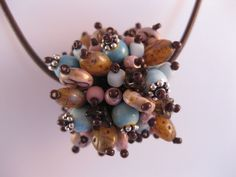 Beaded bead with pinks, browns and powder blues.