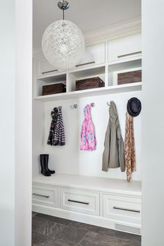 In this renovation, designer Claire Paquin reconfigured a powder room and hall closet to make space for a mudroom the original house lacked. The clean, transitional space is light and bright, with all-white millwork and built-in storage that extends to the ceiling to maximize space. A fun, modern pendant continues the clean white color scheme.