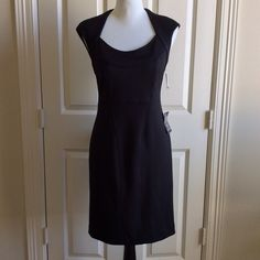 Donna Morgan Black Cut Out Dress This sophisticated black dress has the following features: round neckline, cut out back design, one button with hook eye and zipper closure in back, seaming detail on bodice, measures 37 inches from shoulder to hem, 93% polyester 7% spandex, Size 8 Donna Morgan Dresses