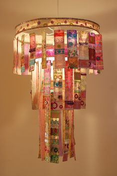 Three-tier chandelier made from paper mache strips of handmade paper, adorned with sequins, beautiful papers & colorful trimmings.