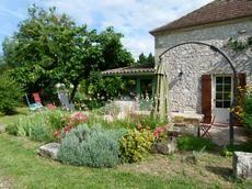 La terrasse côté piscine très fleuries, avec salon de jardin, parasol, BBQ et transats.  Elle a un accès direct sur la cuisine et le salon.